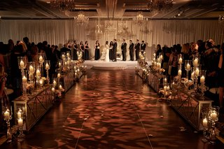 ivory-drapery-and-chandeliers-over-altar-area-patterned-lighting-on-aisle-mirrored-details