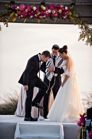 groom-steps-on-glass-during-outdoor-oceanfront-jewish-wedding