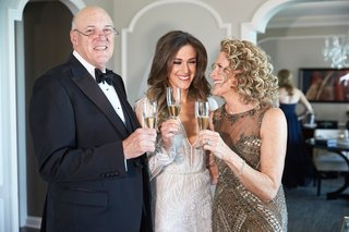 bride-in-inbal-dror-wedding-dress-with-mother-and-father-tuxedo-gold-gown-champagne-flutes-cheers
