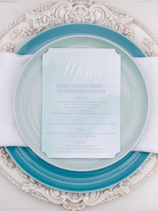 white-and-blue-menu-on-white-napkin-blue-plate-and-white-detailed-charger-plate