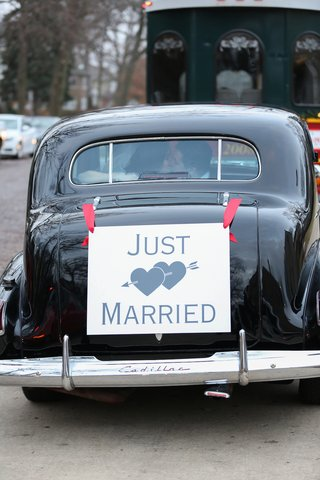 just-married-car-with-sign-tied-with-red-bows-and-bride-and-groom-kissing-in-back-window