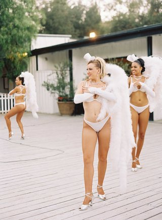 women-in-bras-and-underwear-with-unique-feather-headpieces-during-cabaret-show-at-wedding-reception
