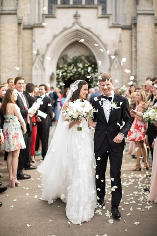 bride-in-lace-trim-veil-and-groom-walking-out-of-church-flower-petal-toss-before-walking-reception