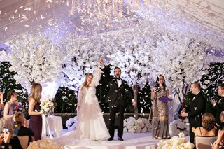bride-and-groom-husband-and-wife-hands-raised-white-confetti-canon-white-cherry-blossom-trees