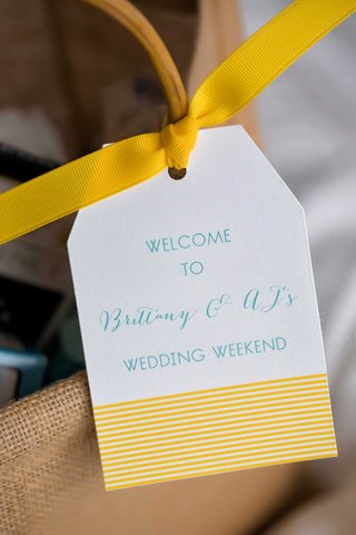 yellow-and-blue-welcome-bag-tag-for-wedding-weekend-tied-with-bright-yellow-grosgrain-bow