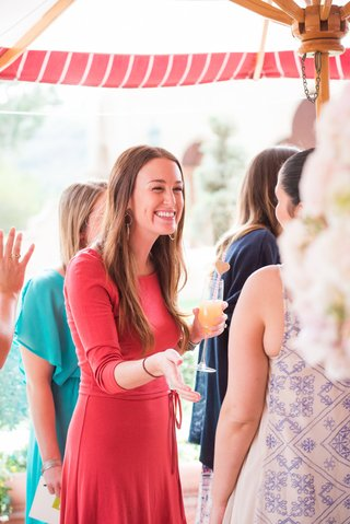 bridal-shower-guest-in-red-dress-holds-mimosa-in-a-champagne-flute-pink-and-white-straw-gold-heart