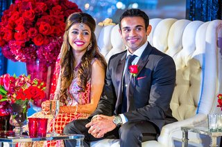 indian-newlyweds-on-tufted-white-loveseat-at-reception