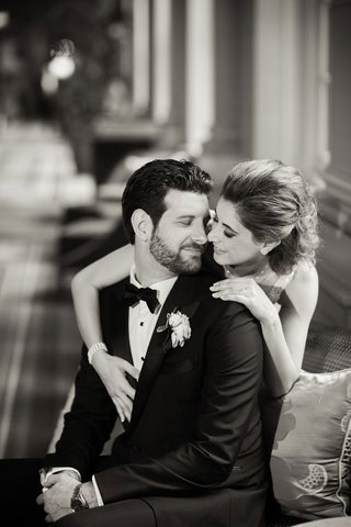 black-and-white-photo-of-bride-in-anne-barge-dress-and-groom-in-tuxedo-and-bow-tie-arm-draped-over