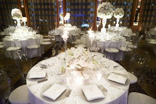 white-tables-and-centerpieces-ghost-chairs-crystal-chargers-white-ivory-flowers