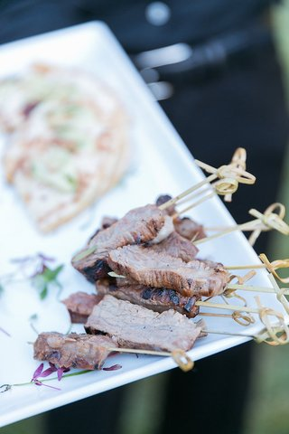 wedding-appetizers-of-pieces-of-grilled-beef-on-skewers-on-white-tray-passed-by-server