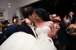 bride-in-nardos-deisgns-lace-mermaid-gown-holding-red-rose-held-by-groom-kisses-bubbles