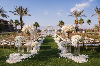 grass-lawn-wedding-ceremony-white-flower-petals-tall-white-flower-arrangements-gold-chairs-palm-tree