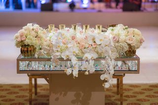 sweetheart-table-with-glass-layers-crystals-in-between-orchid-rose-flower-arrangement-candles-gold
