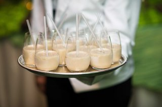 server-at-wedding-holding-silver-tray-of-kahlua-milkshake-with-clear-straw-desserts