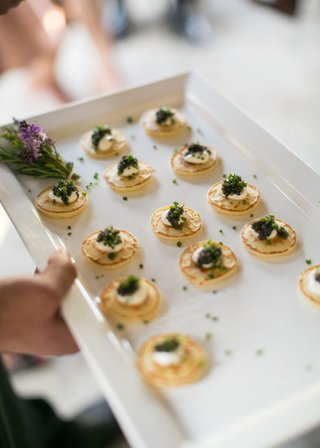 ranch-wedding-cocktail-hour-with-a-tray-of-small-pancakes-caviar-chives-cream