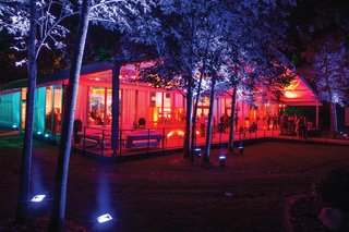 wedding-reception-in-a-glass-tent-structure-with-covered-terrace-lit-in-red-yellow-light