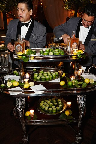 large-bar-cart-with-hollowed-out-limes-for-shot-glasses-tequila-tequila-herradura-and-limes-servers