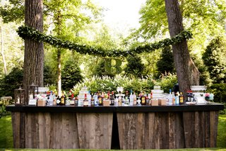 wood-bar-at-outdoor-cocktail-hour-between-trees-garland-with-moss-monogram-in-between-trees