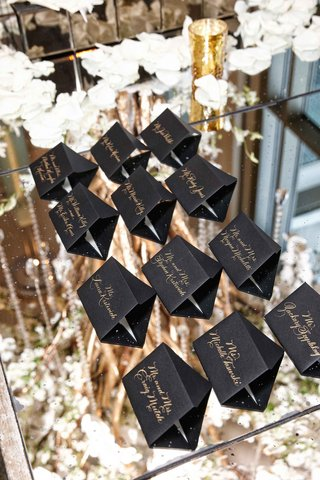 black-escort-cards-on-glass-mirror-table-with-gold-calligraphy