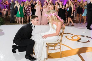 bride-in-fake-pink-flower-crown-while-groom-removes-garter