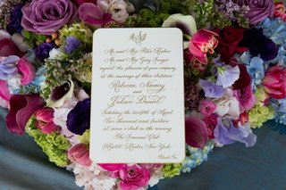 white-wedding-invitation-with-gold-calligraphy-in-a-bed-of-colorful-flowers