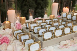 framed-seating-cards-surrounded-by-candles-and-petals