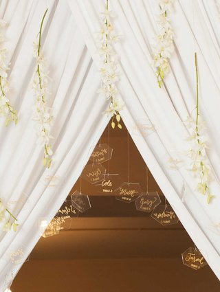 clear-geometric-shaped-escort-cards-suspended-from-hanging-fabric-and-long-stems-with-white-blooms