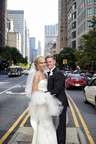 bride-in-strapless-elizabeth-fillmore-wedding-dress-and-groom-in-tuxedo-in-middle-of-chicago-street