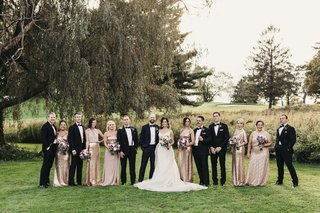 bridal-party-portrait-outdoors-groomsmen-in-black-tuxes-bridesmaids-in-rose-gold-dresses
