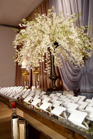 wedding-place-card-table-with-a-mirror-tabletop-and-hawaiian-orchids-in-a-tall-vase