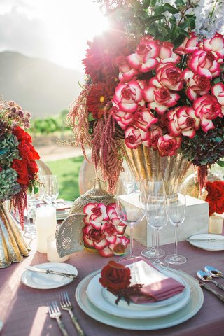 red-and-dark-purple-flowers-floral-arrangements-in-gold-vases-on-pink-table-linens-and-lanterns