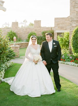 bride-in-long-sleeve-ball-gown-with-tuxedo-groom-outside