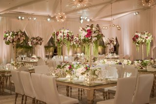 wedding-reception-mirror-gold-table-with-white-chairs-and-tall-flower-arrangements-amaranthus-red