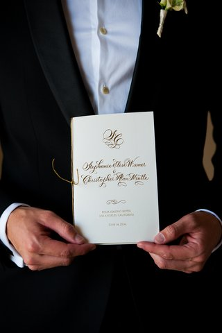 groom-holding-white-ceremony-program-with-gold-lettering