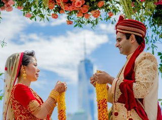 bride-and-groom-indian-wedding-ceremony-outdoor-new-york-skyline-view-flowers-red-ensembles