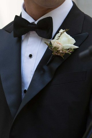 groom-tuxedo-and-bow-tie-with-white-rose-and-small-pink-rose-bud-boutonniere