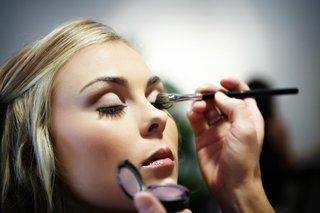 bride-having-makeup-artist-put-on-eyeshadow-for-wedding