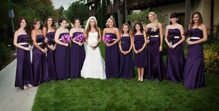 bride-with-bridesmaids-in-long-purple-dresses-on-hotel-lawn