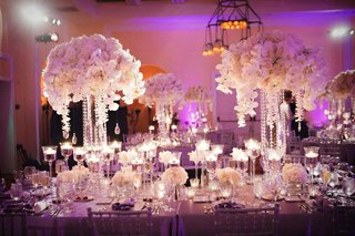 tall-white-centerpieces-with-floating-candles-and-purple-lighting