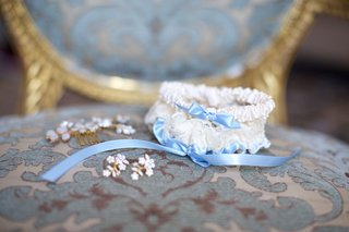 wedding-day-garter-white-lace-satin-with-light-blue-ribbon-on-blue-chair-gold-details
