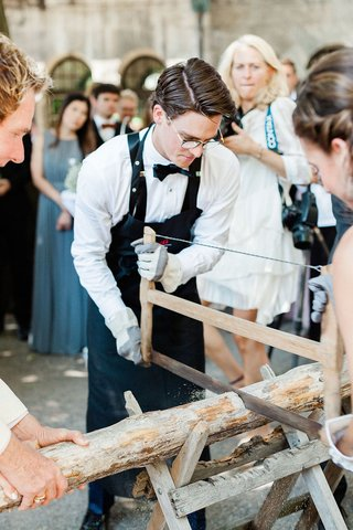 bride-and-groom-sawing-log-in-half-after-germany-wedding-ceremony-german-traditions
