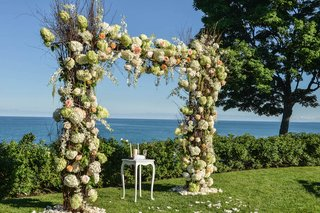 ceremony-arch-with-white-pink-and-green-flowers-in-front-of-lake