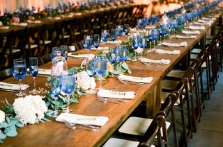 wedding-reception-long-farm-tables-wood-with-wood-chairs-garland-down-center-greenery-blue-glasses