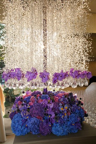 tall-floral-arrangement-featuring-blue-pink-and-purple-flowers-and-hanging-white-flowers-crystals