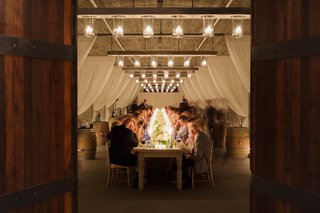 guests-in-vineyard-wine-barrel-room-at-long-table