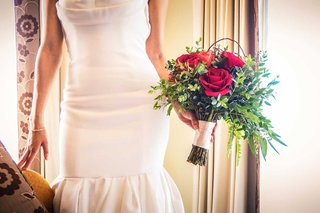 a-bride-holding-a-bouquet-of-red-roses-and-leafy-greenery