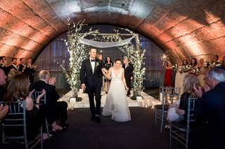 wedding-ceremony-bride-and-groom-holding-hands-walking-up-aisle-granite-arch-bridesmaids-guests