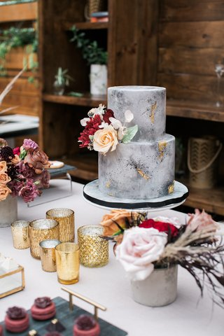 small-two-tier-grey-marble-cake-made-to-look-like-concrete-with-gold-foil-and-fresh-flowers