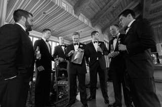 black-and-white-photo-of-groom-opening-wedding-gift