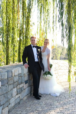 bride-and-groom-on-stone-bridge-in-wedding-attire